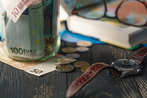 currency in a jar with watch