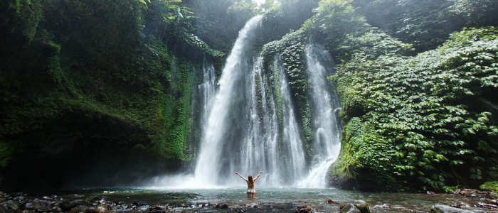Girl underneath Bali waterfall