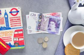 Pound notes, cup of tea and London guide book